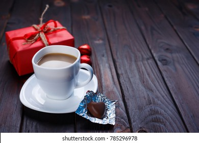 Valentine's Day concept. Cup of coffee with heart shaped chocolates and gift box on wooden table, copy space