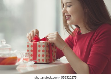Valentine's Day concept. festive breakfast. Valentine's Day holiday. Tea and bouquet of red flowers on a table by the window. girl prints gift