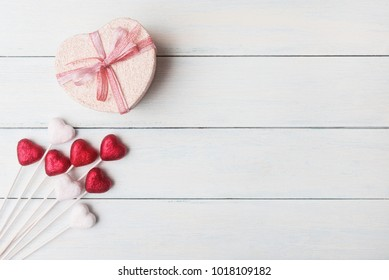 Valentines day concept with gift box and heart shaped decorations.