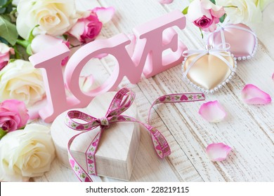 """Valentine's day concept with gift box, letters """"love"""" and flowers on old vintage wooden background."""
