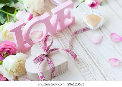 """Valentine's day concept with gift box, letters """"love"""" and flowers on old vintage wooden background"""