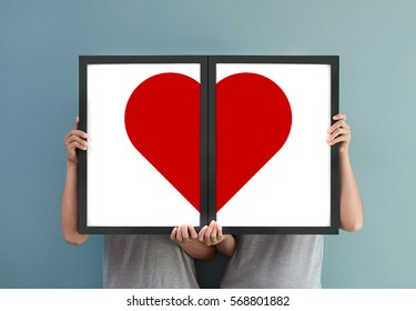 Valentines day concept. Happiness of couple holding red heart in picture frames.