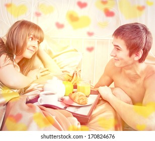 Valentine's day concept. Happy man and woman having luxury hotel breakfast in bed together
