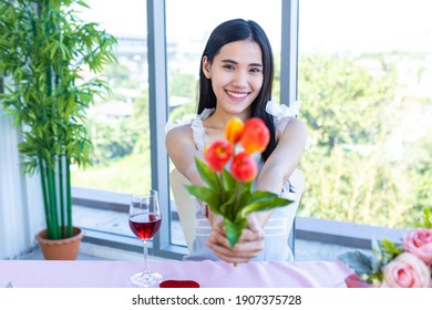 Valentine's day concept, Happy of smiling Asian young female sitting at a table food holding a fake flower vase at in the restaurant background