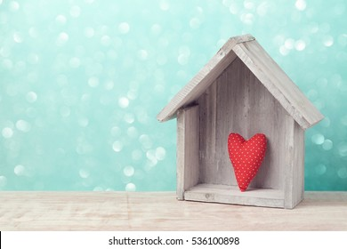 Valentine's day concept with heart shape and house over rustic background