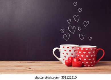 Valentine's day concept with hearts and cups over chalkboard background