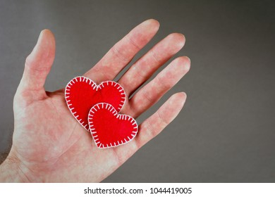 Valentine's Day Concept hearts in hand on a gray background