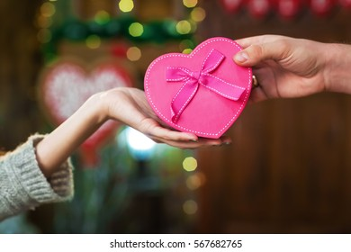 Valentine's Day concept. A loving couple celebrating Valentine's Day. Lovers give each other gifts
