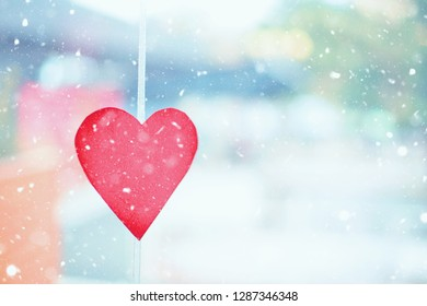 Valentine's day concept on a snowy winter day. decor of carved red paper in the form of a heart