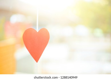 Valentine's day concept on a Sunny day. decor of carved red paper in the form of a heart