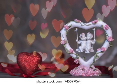 Valentine's Day concept: a pair of angels on a swing with roses. The background of the heart-bokeh