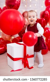valentine's day concept - portrait of funny baby girl with red balloons and big gift box