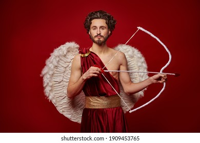 Valentine's Day concept. Portrait of the God of love - Cupid with bow and arrow on a red background.
