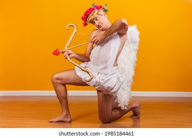 Valentine's day concept. Portrait of the God of love - Cupid with bow and arrow on a yellow background.
