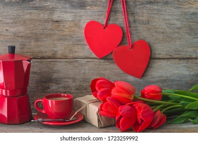 Valentine's day concept. Red cup of coffee, geyser coffee maker, handmade gift box, bunch of red tulips and two hearts decoration on old non paint wooden background