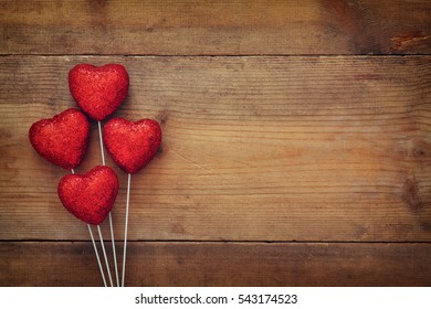 Valentines day concept. red glitter hearts on wooden background. Flat lay composition