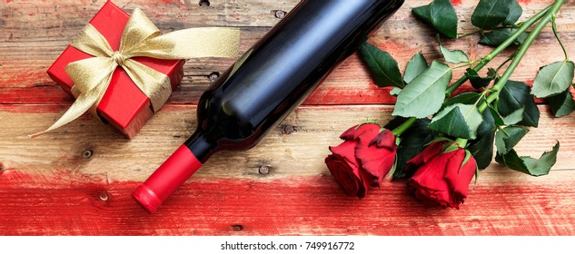 Valentines day concept. Red wine bottle, roses and a gift on wooden background