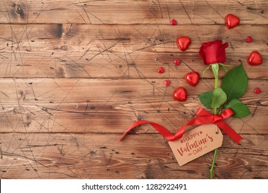 Valentine's day concept with rose flower and heart shape chocolate on wooden background. Top view from above. Flat lay