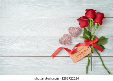 Valentine's day concept with rose flowers, gift tag and glitter heart shapes on wooden background. Top view from above. Flat lay