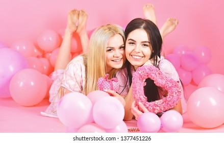 Valentines day concept. Sisters, friends in pajamas at pajamas party. Girls lay near balloons, holds heart toys, pink background. Blonde and brunette on smiling faces dreaming about love and date.