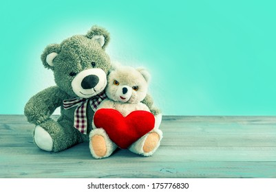 Valentines Day concept. Teddy Bears couple with red heart. Hipster style toned picture with mint green background