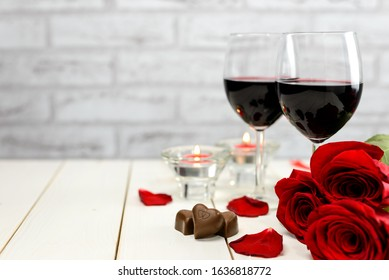 Valentine's Day concept. Two glasses of wine, red roses, chocolate hearts, rose petals and burning candles on a white wooden table with copy space for text. Selective focus.