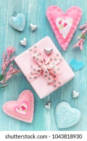 Valentine's Day concept with twrapped gift box and many different hearts on turquoise color wooden background