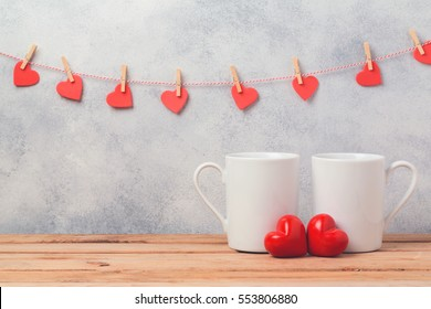 Valentines day concept with white coffee cups and heart shapes over rustic background with garland