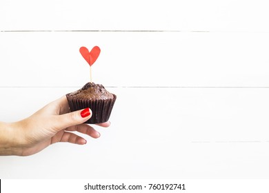Valentine's Day concept. A woman holds a chocolate capcake in her hand with a paper heart on a stick. Background