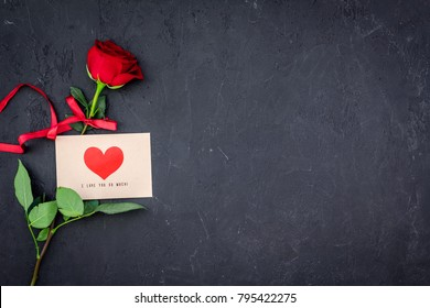 Valentine's day congratulation. Red rose and greeting card with heart sign on black background top view copy space