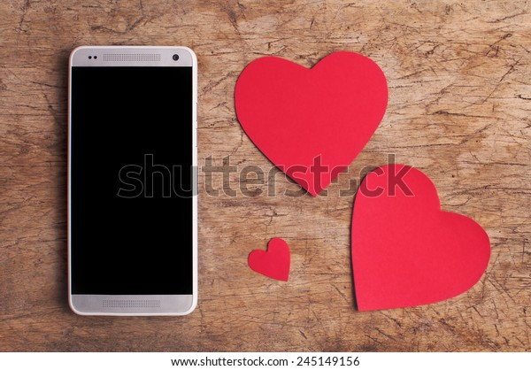 Valentine's Day copy space on smart phone with blank screen and red paper hearts on old wooden table