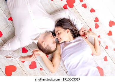valentine's day, a couple in love lies among the hearts on the floor hugging