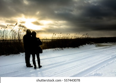 Valentine's day couple, romantic landscape in winter over lake at sunset