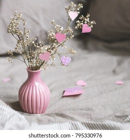 Valentines day decoration with copy space. Dried flowers in pink vase with hearts. Selective focus.