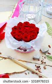 Valentine's Day decorations: box with red roses, vintage paper for greetings, wooden and wicker hearts.