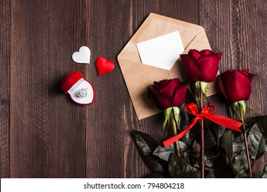 Valentines day envelope love letter with greeting card engagement ring in box mothers day red rose gift surprise on dark wooden background with copyspace. Love flower gift for woman romantic