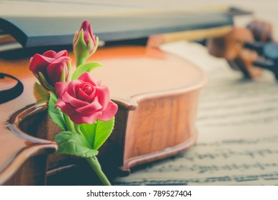 Valentine's day / eternal love or special occasion concept : Artificial three red roses put near a stradivarius type violin on blurred musical notes in a romantic love song sheet music. Vintage style.