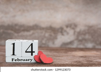Valentines day with february 14th. Wooden white block calendar and Red heart on wood table background with copy space