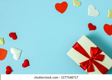 Valentines day flat lay copy space. On a blue background a gift box and a red bow, red paper hearts, hearts made of white fabric and red satin. In the center is a place for text.
