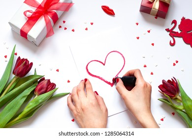 Valentine's day flat lay. Woman's hands drawing a heart with red lipstick. Romantic concept composition with flowers and cupid. Top view