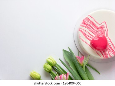 Valentine's Day. Frame made of flowers, Heart shaped mousse cakes  on white background. Flat lay, top view, copy