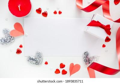 Valentinstag. Rahmen aus Geschenken, Kerze, roten Herzen auf weißem Hintergrund. Valentinstag Hintergrund. Flachlage, Draufsicht, Kopienraum.
