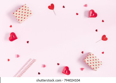 Valentine's Day. Frame made of gifts, candles, confetti on pink background. Valentines day background. Flat lay, top view, copy space.