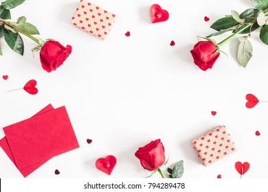 Valentine's Day. Frame made of rose flowers, gifts, candles, confetti on white background. Valentines day background. Flat lay, top view, copy space.