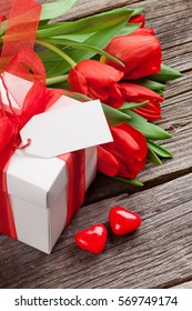 Valentines day gift box and red tulips on wooden table