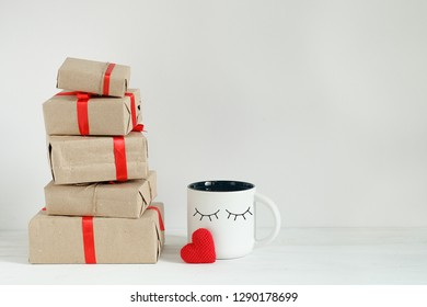 Valentines day gift boxes, toy heart and kawaii coffee cup with cutest funny eyes on white background, cute holiday breakfast concept with copy space