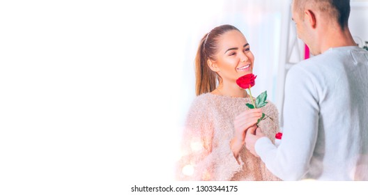 Valentines Day Gift. Handsome young man giving red rose flower Gift to his Girlfriend. Young Couple holding rose and smiling. St. Valentine's Day, Love. Hands in Hands, romance, dating concept.