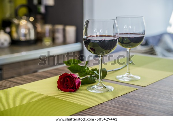 Valentines day: glasses of vine, red roses, for romantic evening. Red rose and wine glasses.