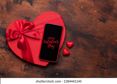 Valentine's day greeting card with candy hearts, gift box and smartphone on wooden background. Top view with space for your greetings or smart phone app. Flat lay