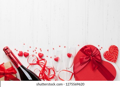 Valentine's day greeting card with champagne and love gift box on wooden background. Top view with space for your greetings. Flat lay